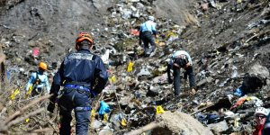 French gendarmes and investigators, seen in this picture released by the French Interior Ministry, make their way through debris from wreckage on the mountainside at the crash site of an Airbus A320, near Seyne-les-Alpes